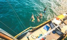 Satellietbeeld van gelukkige millenial vrienden die van zeilboot op overzeese oceaanreis samen binnen springen - Rijke kerels en  royalty-vrije stock foto