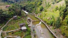 Satellietbeeld van groene terrasvormige padievelden en het voortbouwen op de vallei bij Cat Cat-dorp in Sapa, Vietnam stock video