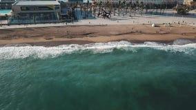 Satellietbeeld van grote turkooise golven en kust dichtbij het strand en de moderne stadsgebouwen voorraad Mooie kust stock footage