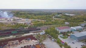 Satellietbeeld van heldergroene gebieden, kleine vijver, huizen en een spoorweg met goederentreinen klem Natuurlijk landschap met stock footage