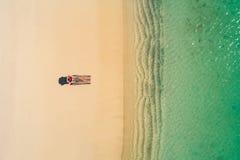 Satellietbeeld van het slanke vrouw zonnebaden die op een strandchairin Seychellen liggen De zomerzeegezicht met meisje, mooie kl royalty-vrije stock fotografie