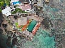 Satellietbeeld van het verbazen weinig surferdorp op de de rotsklip en kustlijn royalty-vrije stock fotografie