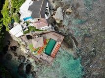 Satellietbeeld van het verbazen weinig surferdorp op de de rotsklip en kustlijn stock afbeeldingen