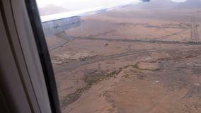 Satellietbeeld van het vliegtuigenvenster op de de de woestijn, bergen en wegen van Egypte stock video