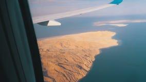 Satellietbeeld van het vliegtuigenvenster op de woestijn van Egypte, de bergen en het rode overzees met duidelijk water stock videobeelden