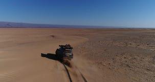 Satellietbeeld van het zwarte auto drijven in de Sahara Geschotene Cinematichommel het vliegen over woestijn stock video