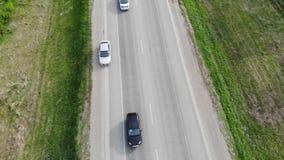 Satellietbeeld van hommel boven auto's het drijven langs lege plattelandsweg op zonnige dag stock footage