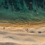 Satellietbeeld van hommel van wilde zandige strand en mensen met azuurblauw hierboven water en zeewier van, aardachtergrond royalty-vrije stock afbeelding