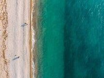 Satellietbeeld van hommel van wilde zandige strand en mensen met azuurblauw hierboven water en zeewier van, aardachtergrond met e royalty-vrije stock afbeeldingen