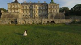 Satellietbeeld van huwelijkspaar die bij oud kasteel dansen stock videobeelden