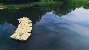 Satellietbeeld van kalm meer met paddleboats op het, met banken voor het sutting op de kust 4K stock footage