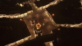 Satellietbeeld van leuk vierkant met verlichte Kerstboom in midden bij nacht stock footage