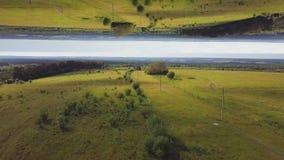 Satellietbeeld van mooie groene weide met bomen en struiken in een zonnige de zomerdag, het effect van de spiegelhorizon stunning stock footage