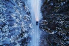 Satellietbeeld van nachtbos door sneeuw, weg en auto wordt behandeld die overgaan die door stock afbeelding