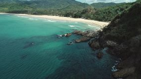 Satellietbeeld van overzeese golven die in de rotsen dichtbij strand verpletteren Hommel van overzeese golven op de gevaarlijke s stock video