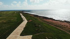 Satellietbeeld van overzeese kustlijn met voetgangers die langs het strand lopen De promenade van Paphoscyprus Hommelmening van O stock video