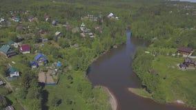 Satellietbeeld van plattelandshuisjedorp en huizen dichtbij de grote die rivier door naald en loofbomen in warm wordt omringd stock video