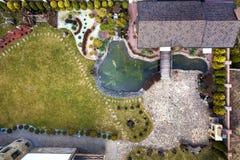 Satellietbeeld van prachtig gemodelleerd complex bezit De daken van recreatie huisvesten plattelandshuisje, vijver op ecologisch  royalty-vrije stock fotografie