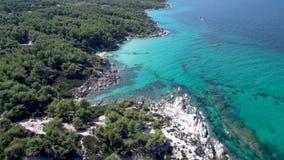 Satellietbeeld van rotsachtig strand met turkoois water in Halkidiki Kavourotripes, Griekenland, stijgende beweging door hommel,  stock video