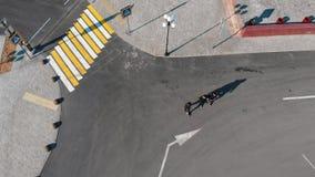 Satellietbeeld van stedelijke straten crosswalk Drie mensen die op de weg lopen stock footage