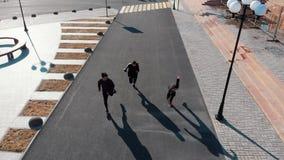 Satellietbeeld van stedelijke straten Drie mensen die op de weg lopen stock footage