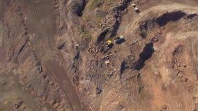 Satellietbeeld van werkend graafwerktuig in de bovengrondse mijn Cameravlucht over industrieel landschap stock video