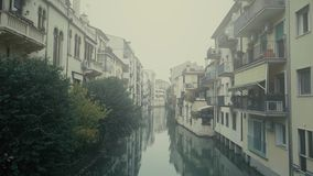 Satellietbeeld van woonhuizen langs smal kanaal in mist Padua, Italië stock videobeelden