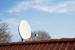 Satellietschotel op het rode dak Stock Foto