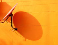 Satellietschotel op oranje muur Stock Afbeeldingen