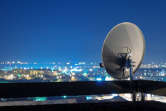 Satellietschotelantenne bovenop het gebouw bij nacht royalty-vrije stock foto