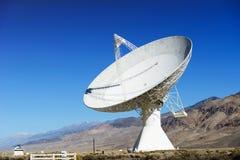Satellit- disk i öken/klar blå himmel Arkivfoton