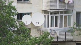 Satellit- disk på väggen av en flervånings- byggnad lager videofilmer