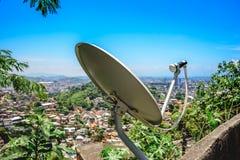 Satellit- maträtt, antenn på bakgrunden av slumkvarterhus arkivbild