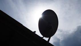 Satellit- maträtt för kontur med solljus på taket Arkivbild