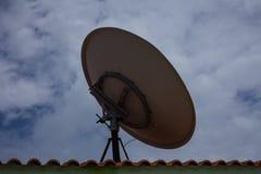 Satellit- maträtt för rund television ovanför det bricked taket Vända mot den molniga blåa himlen Ge det klara mottagandet av tel arkivfoton