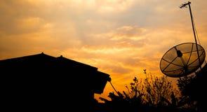 Satellit- maträtt och antenn på taket på solnedgången Royaltyfri Foto