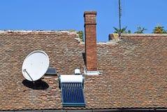 Satellit- maträtt och sol- värmeapparat på taket Arkivfoton