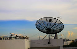 Satellit- maträtt på överkanten av byggnaden arkivfoton