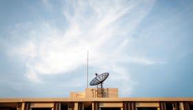 Satellit- maträtt på byggnadstaket med himmelbakgrund Royaltyfri Bild