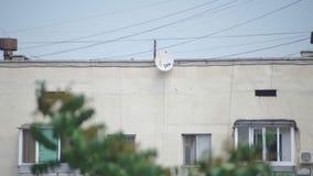 Satellit- maträtt på väggen av en flervånings- byggnad arkivfilmer