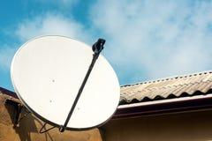 Satellit- maträtt på väggen av ett landshus royaltyfri fotografi