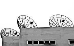 Satellit- maträtt tre på grå byggnad med vit Arkivbild