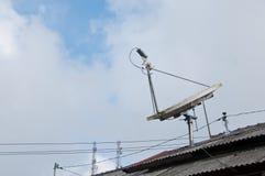 Satellite a alta tecnologia moderno su un tetto con il cielo nuvoloso Immagine Stock