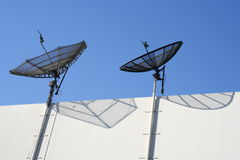 Satellite Antenna. Two satellites perched on top of the side wall of a white building, with bright blue sky in the background Stock Image