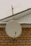 Satellite antenna on the brick wall and the roof of the house. Satellite and analog antenna on the brick wall and the roof of the house Royalty Free Stock Photography