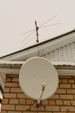 Satellite antenna on the brick wall and the roof of the house. Satellite and analog antenna on the brick wall and the roof of the house Royalty Free Stock Images