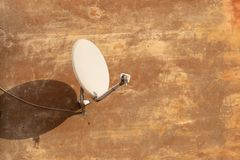 Satellite antenna for receiving digital TV signal on plastered wall royalty free stock photography