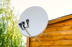 Satellite antenna. On a wooden house outdoors stock images