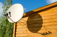 Satellite antenna. On a wooden house outdoors royalty free stock images