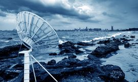 Satellite antenna by the sea. Satellite antenna on the reef on the seashore royalty free stock photography